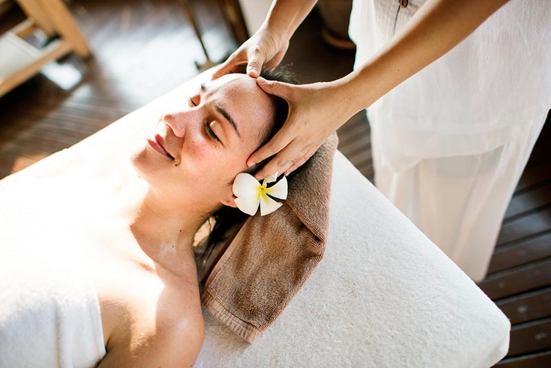 Relaxed lady lying on her back on massage table receiving a head massage