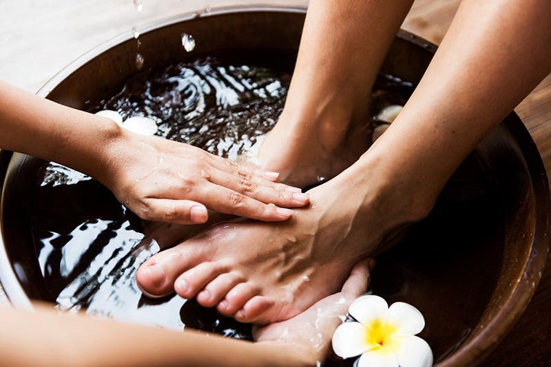 Hands giving a foot massage to a pair of feet in a bowl of water