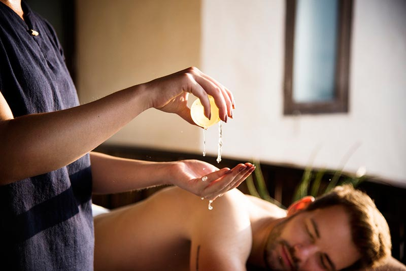 Masseuse preparing massage oil with male lying on massage table awaiting a back massage