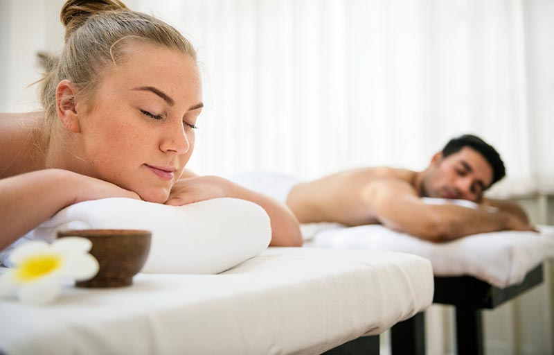 A male and female couple lying down on massage tables waiting for their couples massage to start