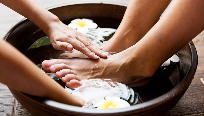 A pair of feet receiving a foot massage in a bowl of water