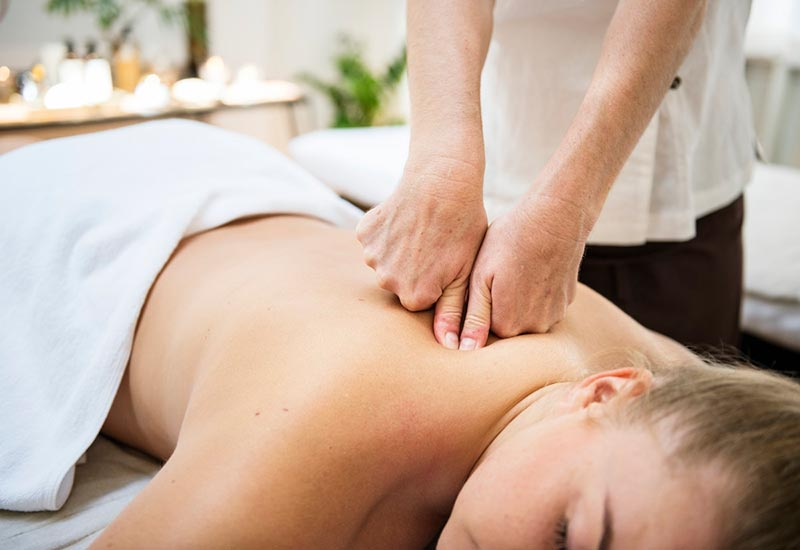 A lady lying face down receiving a back massage with pressure being applied by thumbs and knuckles