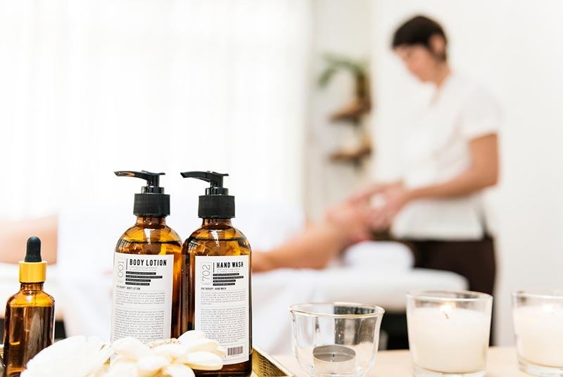 Massage oils and candles with lady lying on back on massage bed receiving a head massage