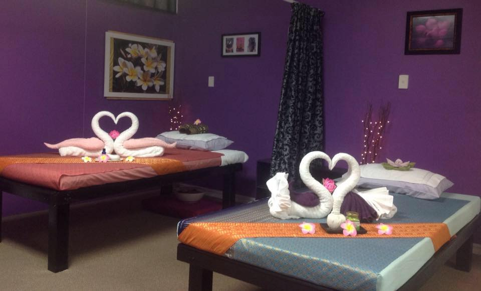 Two massage tables inside Sawaddee decorated with towels shaped into swans forming a heart with their beaks