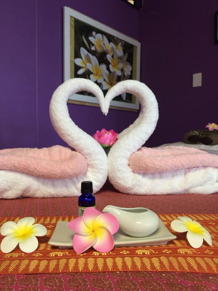Towels shaped into swans forming a heart with their beaks on a massage table inside Sawaddee